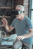 Συγκεντρωμένο ανώτερο άτομο που δοκιμάζει τα γυαλιά VR και που τινάζει τα χέρια στοκ εικόνες