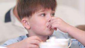 Συγκεντρωμένο μελαχροινό αγόρι τρίχας που τρώει τη σοκολάτα croissant απόθεμα βίντεο