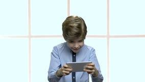 Συγκεντρωμένο μικρό παιδί που παίζει το κινητό παιχνίδι απόθεμα βίντεο