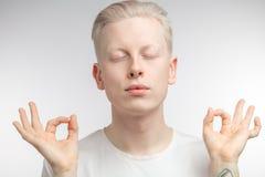 Συγκεντρωμένο ξανθό άτομο με τα μάτια περίβολων που ασκεί τη γιόγκα Στοκ Εικόνες