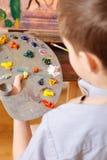 Συγκεντρωμένο παιδί που αναμιγνύει τα χρώματα στο στούντιο τέχνης Στοκ εικόνες με δικαίωμα ελεύθερης χρήσης