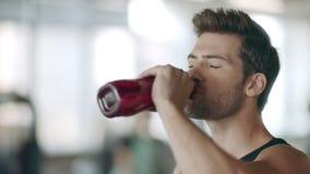 Συγκεντρωμένο πόσιμο νερό ατόμων στη γυμναστική ικανότητας Πορτρέτο του αρσενικού προσώπου αθλητών απόθεμα βίντεο