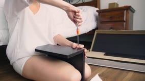 Συγκεντρώνοντας τα έπιπλα στο σπίτι, μια νοικοκυρά συγκεντρώνει ένα γραφείο υπολογιστών χρησιμοποιώντας τα εργαλεία χεριών φιλμ μικρού μήκους