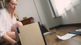 Συγκεντρώνοντας τα έπιπλα στο σπίτι, μια νοικοκυρά συγκεντρώνει ένα γραφείο υπολογιστών χρησιμοποιώντας τα εργαλεία χεριών απόθεμα βίντεο