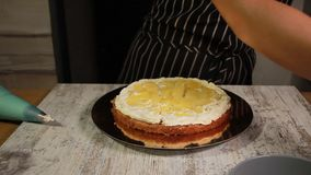 Συγκεντρώνοντας τα στρώματα κέικ καρύδι-μπανανών, λερώνοντας με το σιρόπι, εφαρμόζοντας τη βουτύρου κρέμα, που γεμίζει την πλήρωσ φιλμ μικρού μήκους