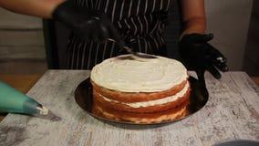 Συγκεντρώνοντας τα στρώματα κέικ καρύδι-μπανανών, λερώνοντας με το σιρόπι, που εφαρμόζει τη βουτύρου κρέμα, γέμισμα επικαλύψεων φιλμ μικρού μήκους