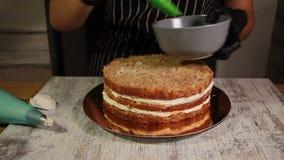 Συγκεντρώνοντας τα στρώματα κέικ καρύδι-μπανανών, λερώνοντας με το σιρόπι, που εφαρμόζει τη βουτύρου κρέμα, επικάλυψη που γεμίζει απόθεμα βίντεο