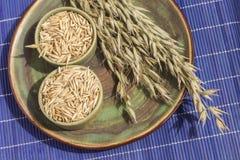 Συγκεντρώστε των βρωμών και του κύπελλου με το σιτάρι σε ένα πράσινο πιάτο Μπλε υπόβαθρο r στοκ φωτογραφία