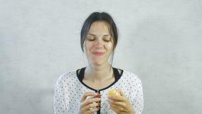 Συγκινήσεις από το γλυκό στο πρόσωπο του κοριτσιού Γυναίκα Brunette που τρώει γλυκό tangerine και το χαμόγελο απόθεμα βίντεο