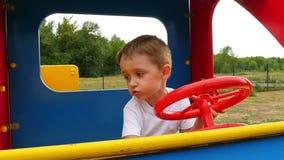 Συγκινήσεις ενός μικρού παιδιού Το αγόρι παίζει τη συνεδρίαση σε ένα ξύλινο αυτοκίνητο στην παιδική χαρά απόθεμα βίντεο