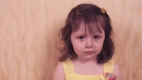 Συγκινήσεις ενός μικρού παιδιού Μικρό κορίτσι σε ένα κίτρινο φόρεμα Πορτρέτο ενός όμορφου κοριτσιού φιλμ μικρού μήκους