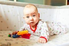 Συγκινήσεις παιδιών ` s Το παιδί είναι στο κρεβάτι και το παιχνίδι με τα παιχνίδια Ένα παιδί ξέρει στο σπίτι τον κόσμο το μωρό μα Στοκ φωτογραφία με δικαίωμα ελεύθερης χρήσης