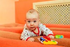Συγκινήσεις παιδιών ` s Το παιδί είναι στο κρεβάτι και το παιχνίδι με τα παιχνίδια Ένα παιδί ξέρει στο σπίτι τον κόσμο το μωρό μα Στοκ Φωτογραφία