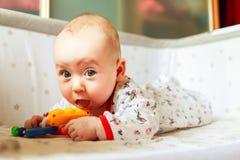 Συγκινήσεις παιδιών ` s Το παιδί είναι στο κρεβάτι και το παιχνίδι με τα παιχνίδια Ένα παιδί ξέρει στο σπίτι τον κόσμο το μωρό μα Στοκ Εικόνες