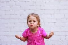 Συγκινήσεις παιδιών ` s Το όμορφο κορίτσι επιδεικνύει πόσο ισχυρή είναι Στοκ Εικόνες