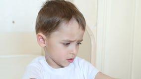 Συγκινήσεις του παιδιού: το αγόρι παρουσιάζει δυσαρέσκεια, καθμένος στον πίνακα φιλμ μικρού μήκους