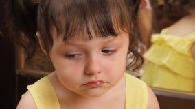Συγκινήσεις του παιδιού Ένα μικρό κορίτσι με τα μεγάλα μάτια φωνάζει Ένα παιδί σε ένα κίτρινο φόρεμα από τον καθρέφτη φιλμ μικρού μήκους