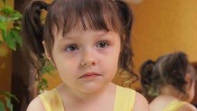 Συγκινήσεις του παιδιού Ένα μικρό κορίτσι με τα μεγάλα μάτια φωνάζει Ένα παιδί σε ένα κίτρινο φόρεμα από τον καθρέφτη απόθεμα βίντεο