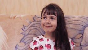 Συγκινήσεις του παιδιού Μικρό κορίτσι σε ένα όμορφο φόρεμα στον καναπέ Κορίτσι σε ένα φόρεμα με τις καρδιές απόθεμα βίντεο