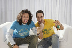 Συγκινημένα άτομα που προσέχουν την τηλεόραση με το μπουκάλι μπύρας Στοκ Φωτογραφίες