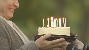 Συγκινημένα κεριά γενεθλίων ηλικιωμένων γυναικών φυσώντας έξω, εορτασμός κομμάτων, μακροζωία απόθεμα βίντεο