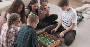 Συγκινημένα κορίτσια ενθαρρυντικά για τους αδελφούς που παίζουν foosball φιλμ μικρού μήκους