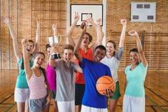 Συγκινημένα παιδιά γυμνασίου που κρατούν το τρόπαιο στο γήπεδο μπάσκετ στοκ εικόνα