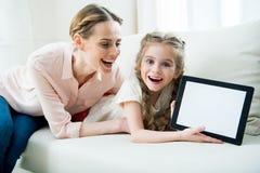 Συγκινημένες μητέρα και κόρη που παρουσιάζουν ψηφιακή ταμπλέτα Στοκ Φωτογραφίες