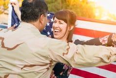 Συγκινημένη γυναίκα με τα τρεξίματα αμερικανικών σημαιών στο αρσενικό στρατιωτικό σπίτι επιστροφής στρατιωτών στοκ φωτογραφία