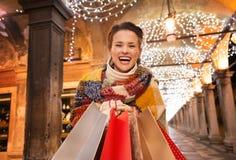 Συγκινημένη γυναίκα με τις τσάντες αγορών που στέκονται κάτω από το φως Χριστουγέννων Στοκ Φωτογραφίες