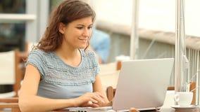 Συγκινημένη γυναίκα που διαβάζει τις καλές ειδήσεις σε ένα lap-top απόθεμα βίντεο