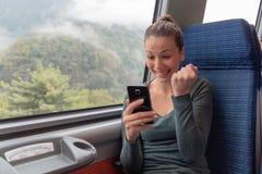 Συγκινημένη γυναίκα που κρατούν ένα smartphone και μια νίκη σε απευθείας σύνδεση στο ταξίδι τραίνων στοκ φωτογραφίες