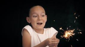 Συγκινημένη εκμετάλλευση κοριτσιών εφήβων στο φωτεινό sparkler χεριών στο μαύρο υπόβαθρο απόθεμα βίντεο