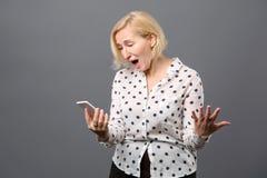 Συγκινημένη η Νίκαια γυναίκα που εξετάζει την τηλεφωνική οθόνη της Στοκ φωτογραφίες με δικαίωμα ελεύθερης χρήσης
