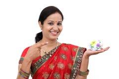 Συγκινημένη ινδική γυναίκα που κρατά μια piggy τράπεζα Στοκ εικόνα με δικαίωμα ελεύθερης χρήσης