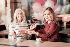Συγκινημένη νέα γυναίκα που χαιρετά την ανώτερη γιαγιά της στα γενέθλιά της Στοκ εικόνα με δικαίωμα ελεύθερης χρήσης