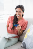 Συγκινημένη συνεδρίαση brunette στον καναπέ της που χρησιμοποιεί το lap-top για να ψωνίσει on-line Στοκ φωτογραφία με δικαίωμα ελεύθερης χρήσης