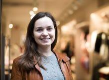 Συγκινημένη τοποθέτηση brunette στην ενδυμασία του καταστήματος και το χαμόγελο Στοκ φωτογραφία με δικαίωμα ελεύθερης χρήσης