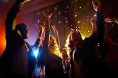 Συγκινημένοι άνθρωποι που χορεύουν στη συναυλία στο νυχτερινό κέντρο  στοκ φωτογραφίες