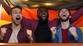 Συγκινημένοι αθλητικοί ανεμιστήρες που κυματίζουν τη γερμανική σημαία στο μπαρ, τη νίκη εθνικών ομάδων φιλμ μικρού μήκους
