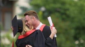 Συγκινημένοι αρσενικοί και θηλυκοί πανεπιστημιακοί πτυχιούχοι που ανταλλάσσουν τα συγχαρητήρια, αγκάλιασμα φιλμ μικρού μήκους