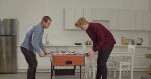 Συγκινημένοι αρσενικοί φίλοι που παίζουν το επιτραπέζιο ποδόσφαιρο εσωτερικό απόθεμα βίντεο