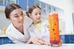 Συγκινημένοι επιστήμονες σπουδαστών δασκάλων και κοριτσιών γυναικών που εξετάζουν τον πειραματικό σωλήνα στο εργαστήριο στοκ φωτογραφίες με δικαίωμα ελεύθερης χρήσης