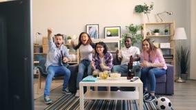 Συγκινημένοι κορίτσια και τύποι που προσέχουν τον αθλητισμό στο σπίτι απόθεμα βίντεο