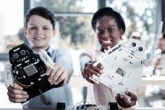 Συγκινημένοι μαθητές που θέτουν με τα ρομπότ τους από κοινού Στοκ φωτογραφία με δικαίωμα ελεύθερης χρήσης