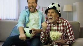 Συγκινημένοι μπαμπάς και γιος ενθαρρυντικοί για την αγαπημένη ομάδα ποδοσφαίρου, παιχνίδι προσοχής στη TV απόθεμα βίντεο