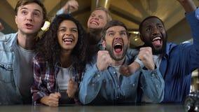 Συγκινημένοι νέοι που υποστηρίζουν την ομάδα, που προσέχει τον αγώνα μαζί, που χαίρεται τη νίκη απόθεμα βίντεο