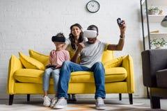 συγκινημένοι πατέρας και κόρη που παίζουν τα τηλεοπτικά παιχνίδια ενώ συνεδρίαση μητέρων πίσω στοκ εικόνες