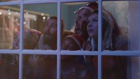 Συγκινημένοι φίλοι που κοιτάζουν έξω στο παράθυρο κατά τη διάρκεια των Χριστουγέννων απόθεμα βίντεο