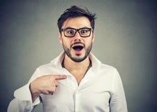 Συγκινημένος έκπληκτος νεαρός άνδρας που δείχνει σε τον στη δυσπιστία Στοκ Φωτογραφία